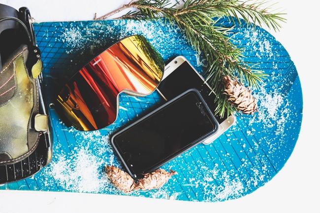 Smartphones liegen auf Snowboard