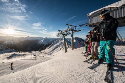 Gruppe Skifahrer schaut auf die sonnige Piste
