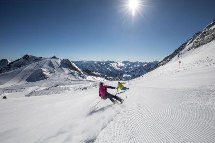 Zwei Skifahrer auf weißer Piste