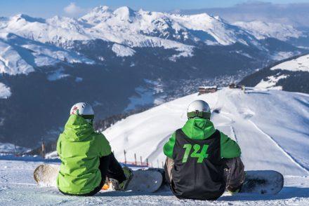 Zwei Snowboarder schauen auf die sonnige Piste