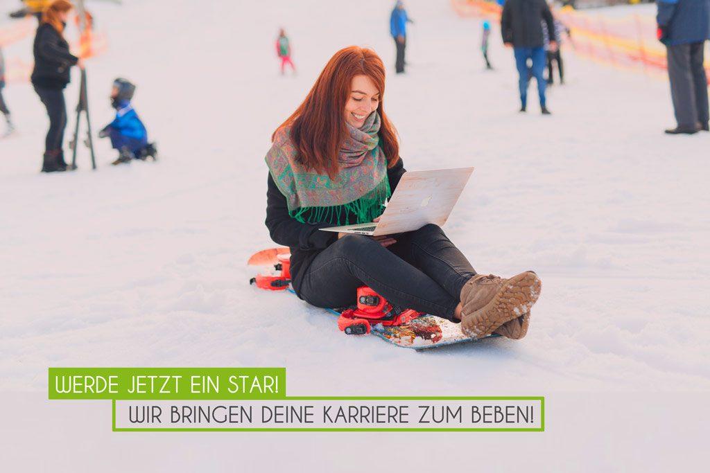 Frau sitzt auf dem Schnee mit Laptop