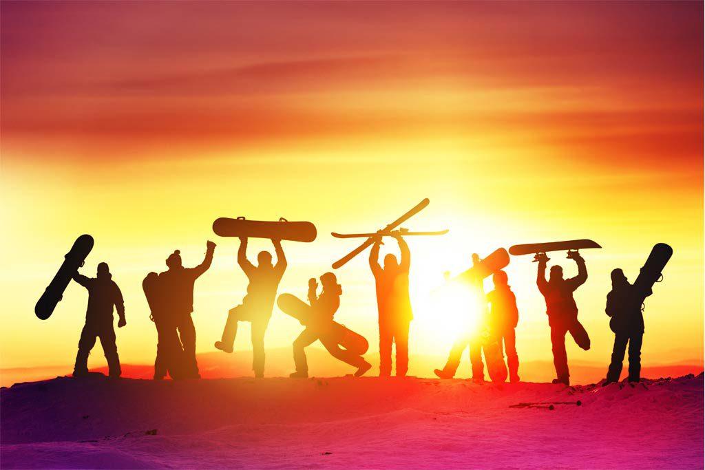 Snowboardergruppe freut sich bei Sonnenuntergang