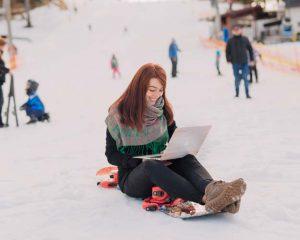 Frau im Schnee am Laptop